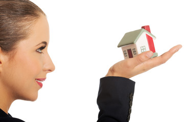 Woman with small model house on hand