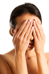 Nude woman covering her eyes because of shame