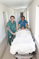 Male and female doctors moving patient on bed along hospital corridor