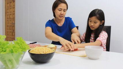 Asian daughter helping mother to slice up vegetables in kitchen