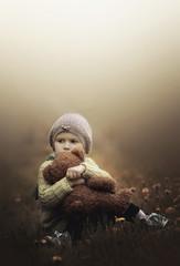 Girl cuddling teddy bear