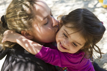 Mother and daughter (4-5) embracing outdoors