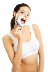 Happy woman shaving her face