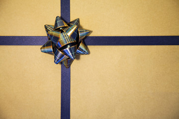 Gold gift wrapped with blue bow