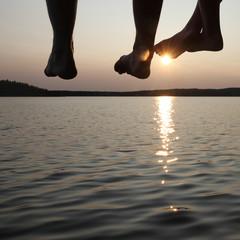 Legs dangling from a pier