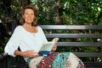Senior woman relaxing in the garden with a book