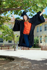 Young female graduate jumping in the air