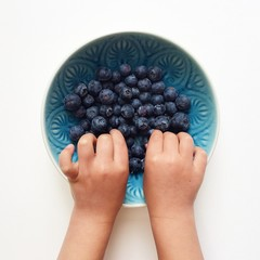 Childs hands in a bowl of blueberries