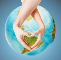 human hands showing heart shape over earth globe