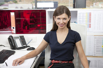 Portrait of young businesswoman sitting at desk in office