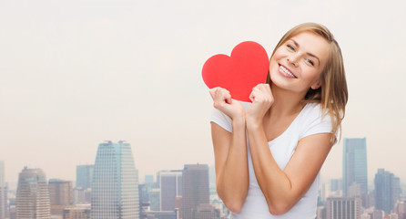 smiling woman in white t-shirt holding red heart