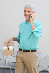 Businessman holding container with coffee cups and talking on mobile phone