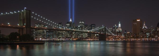 USA, New York, New York City, Illuminated skyline with Brooklyn Bridge blue rays of light