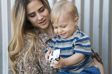 Mother watching her child (12-17 months) play with toy car