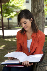 Young woman sitting under a tree reading a book