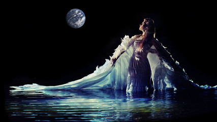 Beautiful white angel is standing in the water.