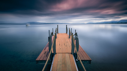 Switzerland, Vaud, Morges, Pontoon pier with wooden flooring in still lake