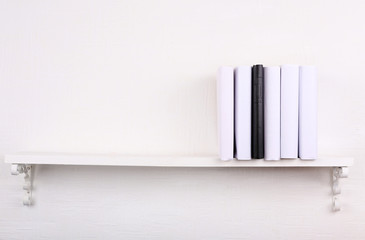 Blank books with black one on bookshelf on white wall