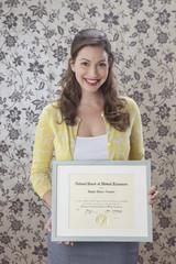 Woman holding framed medical certificate