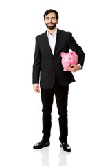 Businessman holding a piggy bank.