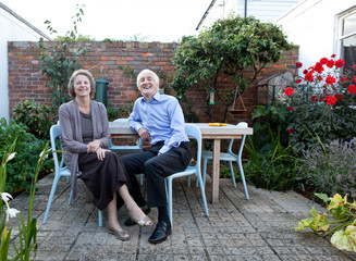 Husband and wife relaxing in garden