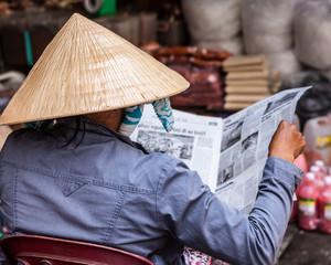 Vietnam, Ho Chi Minh City, Woman reading newspaper