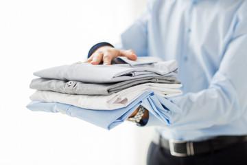 close up of businessman holding folded shirts