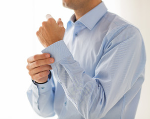 close up of man fastening buttons on shirt sleeve