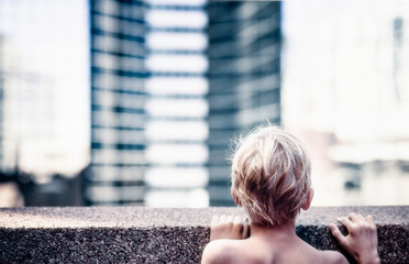 USA, Colorado, Boy (4-5) looking over wall in city