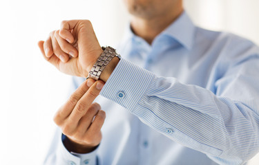 close up of man in shirt fastening wristwatch