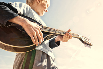 USA, Colorado, Boy (6-7) playing mandolin outdoors