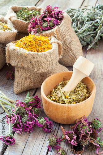 Healing herbs in wooden mortar and in hessian bags, herbal medic