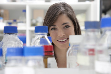 Female lab technician looking through glass recepticles