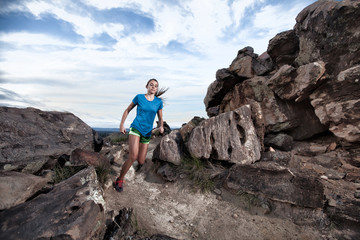 USA, Colorado, Young woman cross-country running on rocky terrain