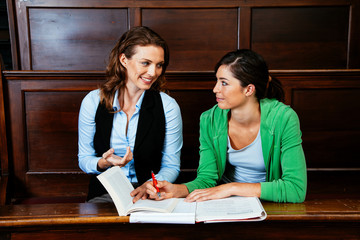 Young woman studying with  her teacher