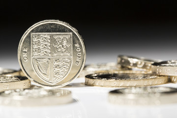 Shiny new UK pound sterling coin balancing around other coins