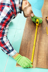 Carpenter worker installing laminate flooring in the room