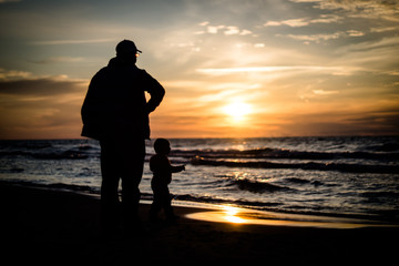 Father and son on beach at sunset