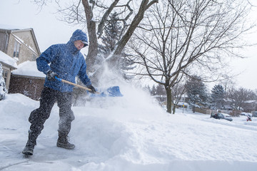 Man Removing Snow from His Driveway with a Shovel