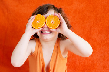 Girl (6-7) holding oranges in front of eyes