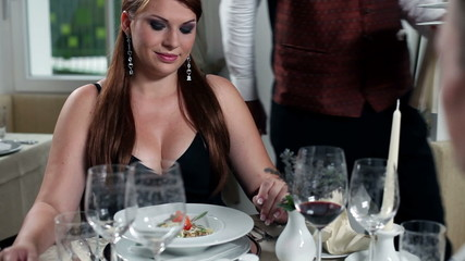 young sexy woman is served by the waiter in beautifull restaurant