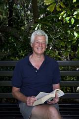 Senior man sitting on garden bench with book