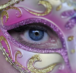 Close up woman blue eye behind the purple mask