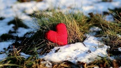 red heart on snowy winter ground