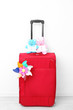 Red suitcase with flower and toys isolated on white