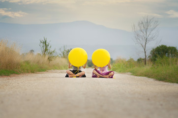 Two girls (6-7, 8-9) with balloons