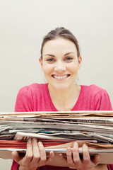 Young woman holding a stack of newspapers