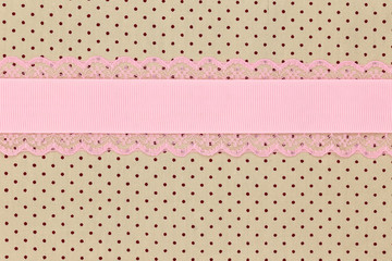Retro beige polka dot textile background with pink ribbon