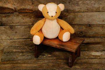 Bear toy on bench on wooden background
