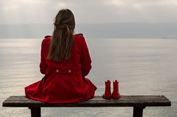 Girl (12-13) in red coat sitting on bench and looking at sea